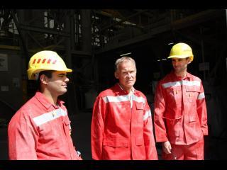 Trois ouvriers en tenue de travail sont debout, devant une usine