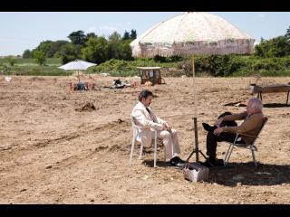 Deux hommes assis dans des fauteuils pliants, sous un parasol, dans un terrain vague
