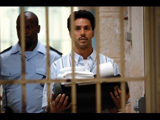 Omar, marchant vers une grille, suivi par un policier