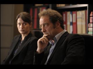 Un homme et une femme, assis dans un bureau, derrière eux, des dossiers