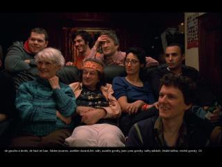 Une famille est réunie sur un canapé et regarde dans la même direction