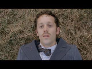 Un jeune homme en costume, l'air hagard, allongé dans un champ