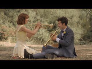 Deux jeunes gens en costumes jouent de la trompette assis par terre en pleine nature
