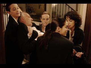 Quatre femmes habillées de noir, portant une homme lui aussi vêtu de noir