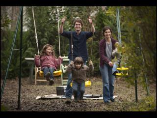 Famille avec trois enfants jouant sur des balançoires