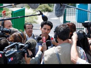 Omar, devant la grille de la prison, interviewé par des journalistes
