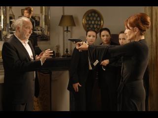 Femme pointant un revolver sur un homme, trois jeunes filles sont spectatrices de la scéne