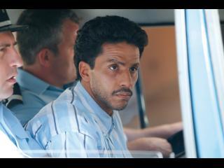 Omar, dans le fourgon de police, entouré de policiers