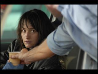 Un bras d'homme tend un café à une femme assise dans une voiture, l'air déboussolée