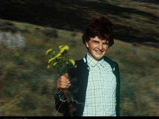 Petit garçon portant un bouquet de fleurs, dans la nature