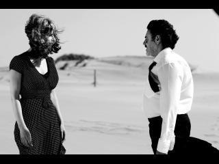 Photo en noir & blanc d'un homme et d'une femme, face à face, dans une étendue déserte