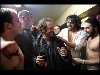 Un homme avec une bouteille de champagne, entouré d'hommes torse nu, dans ce qui semble être un vestiaire sportif