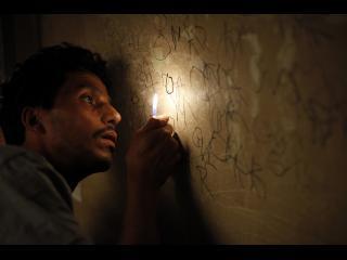 Omar, gravant des inscriptions sur les murs de sa cellule