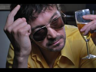 Homme portant des lunettes de soleil en train de boire une coupe de champagne