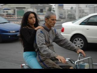 Jeune fille assise derrière son père sur un scooter