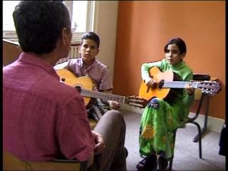 Rachid Guerbas enseignant la musique arabo andalouse à deux enfants
