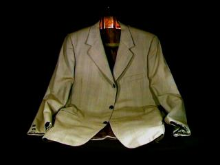 Une veste de costume beige posée sur un fond noir