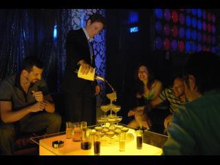 Homme servant une fontaine de champagne à quatre personnes, dans un bar lounge