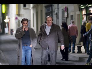 Le commissaire Bellamy marchant dans la rue avec un homme