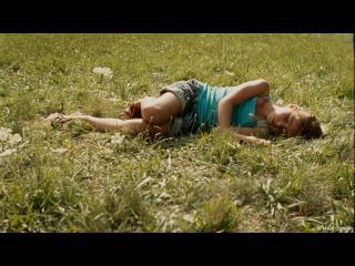 Une petite fille est allongée dans l'herbe