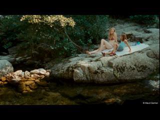 Une femme et une petite fille sont allongées sur un rocher qui surplombe une rivière