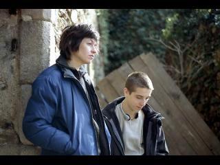 Une femme et un jeune homme se tiennent devant une maison