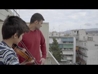 Deux jeunes hommes sur un balcon d'immeuble de cité, le plus jeune joue du violon