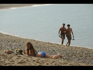 Une jeune fille est allongée sur la plage, deux jeunes hommes passent derrière elle