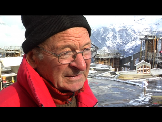 Un ouvrier parle au réalisateur (hors champ), derrière lui, des montagnes à perte de vue