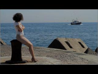 Jeune femme assise, regardant la mer