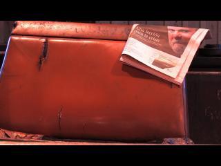 """Sur un siège de train, usé, un journal est disposé, on peut y lire le titre """"Una leccion para la crisis"""""""
