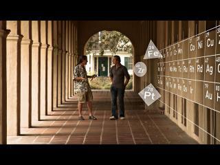 Deux hommes discutent dans un couloir bordé d'arches, sur le mur à leur gauche, le tableau des éléments chimiques