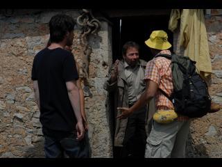 Trois hommes frappent à la porte d'un quatrième qui sort pour leur parler
