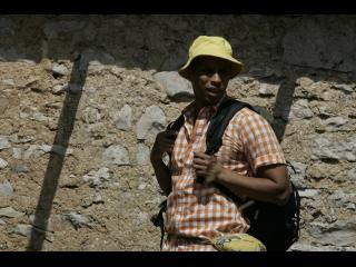 Un homme avec un  sac à dos marche devant un mur en pierre