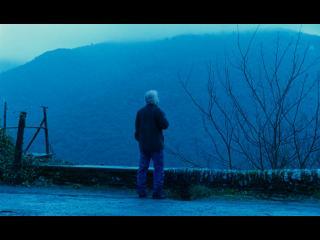 Un homme est debout face à une montagne, au bord d'un chemin, le paysage est bleuté