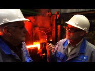 Deux ouvriers en tenue de travail parlent devant une machine de l'usine