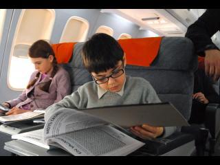 Un garçon, assis à une place d'avion, lit un grand livre posé sur la tablette devant lui