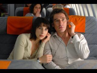 Une femme s'appuie sur l'épaule d'un homme, assis à côté d'elle dans un avion, ils partagent des écouteurs