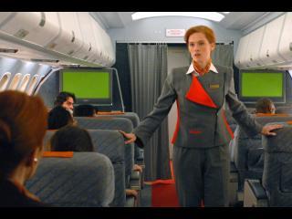 Une hôtesse de l'air vêtue en gris et orange marche le long de l'allée centrale de l'avion