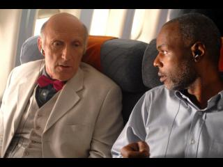 Deux hommes se regardent, pensifs, assis l'un à côté de l'autre dans un avion