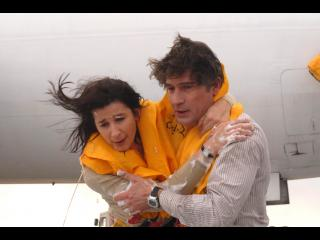 Un homme aide une femme, tous deux sont équipés de gilets de sauvetage, à sortir d'un avion