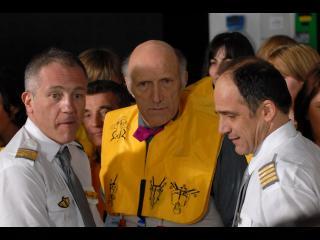 Un homme avec un gilet de sauvetage, entouré par deux pilotes en uniforme, sont debout devant d'autres personnes