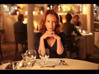 Femme assise à la table d'un restaurant, les mains croisées (Nathalie Baye)