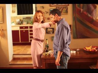 Femme faisant sentir son parfum à un homme, dans la salle à manger d'une maison (Nathalie Baye et Sami Bouajila)