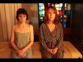 Deux femmes, en pyjama, assises côte à côte sur un lit une place