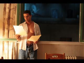 Homme dont la chemise est ouverte, lisant des documents
