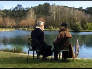 Deux personnes assisent au bord d'un lac, de dos
