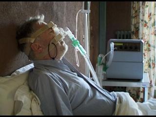 Un homme équipé d'un respirateur, alité