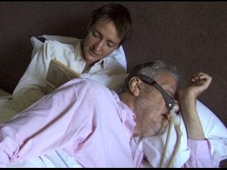 Un homme est allongé sur un lit, derrière lui, une femme aux cheveux courts lit un livre