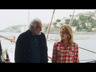 Un homme d'âge mur et une jeune fille se regardent avec complicité, devant un bateau